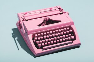 Pink typewriter on a blue pastel bac