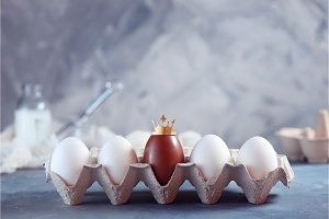 Crowned chocolate Easter egg in a paper carton with white eggs. High key background with copy space. Royalty and uniqueness concept.