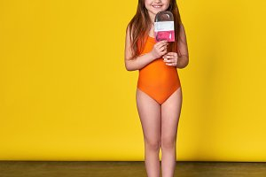 Little girl interracial appearance in orange fashionable swimsuit smiles happy.Beautiful child summer clothes for beach.Advertising, concept summer vacations,travel.Kid brunette, yellow background.