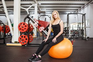 Young sporty slender woman in gym posing on orange ball on a background of gym apparatus