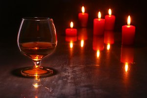 christmas decoration. glass of cognac or whiskey and red candle on a wooden background.