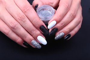 Black, white Nail art manicure. Holiday style bright Manicure with sparkles. Bottle of Nail Polish. Beauty hands. Stylish Nails, Nail Polish