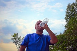 Man is drinking fresh water from a plastic bottle
