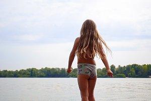 Little longhair girl at riverside
