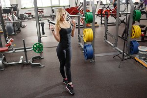 Young sporty woman in gym posing with dumbbells against a lot of gym simulators on background