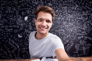 Hipster student doing taking selfie against a big blackboard