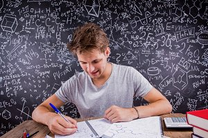 Hipster student doing his homework against a big blackboard