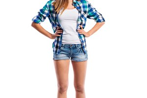 Girl in shorts and shirt, arms on hips, isolated