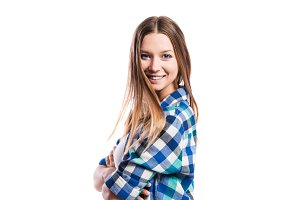 Girl in blue checked shirt, arms crossed, isolated