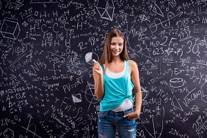 Thinking girl holding head against big blackboard, back view