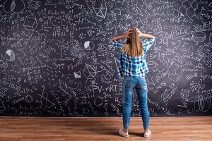 Thinking student holding head against big blackboard, back view