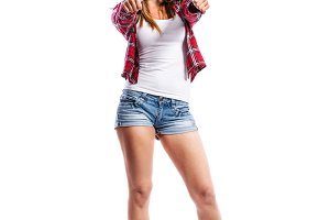 Girl in shorts and checked shirt, thumbs up, isolated
