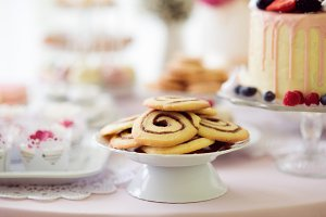 Spiral cookies, cake and cupcakes laid on table.