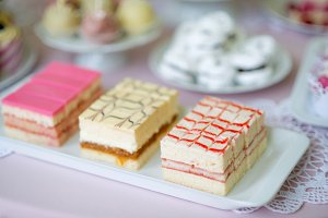 Assortment of different pink mini cream cakes on plate