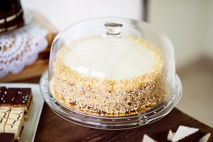 Carrot cake with nuts and glaze on glass cake stand.