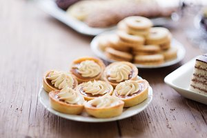 Table with tarts with jam and cream, wooden background.
