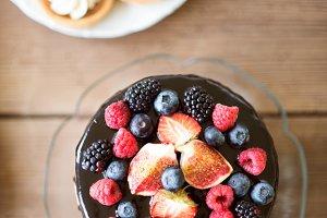 Cake with berries, tarts with cream. Studio shot, wooden backgro