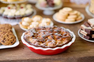 Table with sweet pie, tarts and cookies, wooden background.