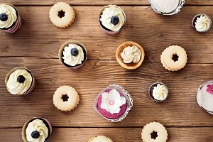 Table with various cupcakes, tarts and cookies. Flat lay.
