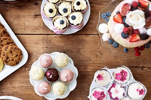 Table with loads of cakes, cupcakes, cookies and cakepops.