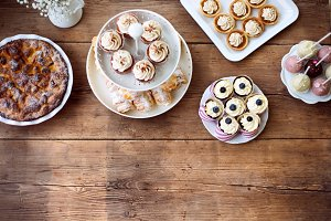 Table with pie, cupcakes, tarts and cakepops. Copy space.