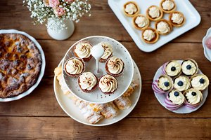 Table with cupcakes, tarts, pie and horn pastries.