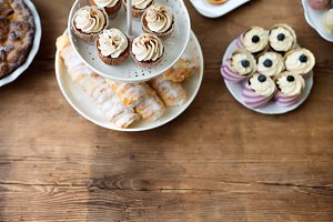 Table with cupcakes, horn pastries, pie and other treats. Copy s