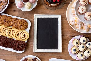 Picture frame and cake, cookies, cakepops, cupcakes. Copy space.