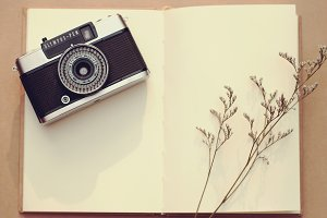 Vintage camera on blank notebook