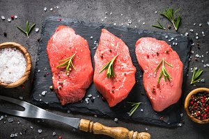 Beef steak with rosemary and spices on black background