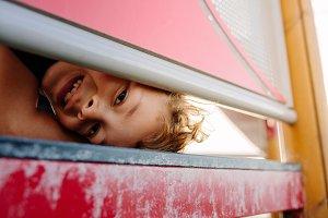 Boy looking through an open frame