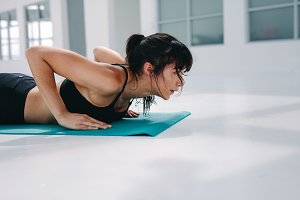 Strong woman doing push ups in gym