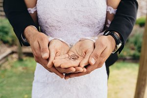 Wedding rings in hands of groom