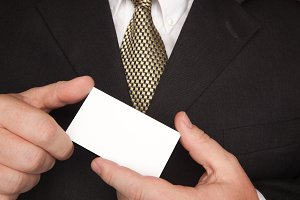 Man In Suit, Tie Holds Business Card