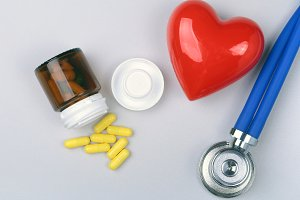 Stethoscope, red heart and assorted pills on white table with space for text.