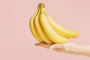 Hand with bunch of bananas