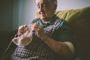 Elderly woman sewing at home