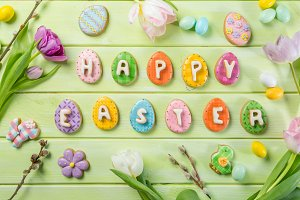 Easter concept - cookies with flowers on green wood background
