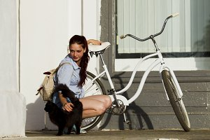 Girl with a black cat and a bike
