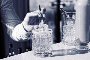 Barman is adding ice to cocktail