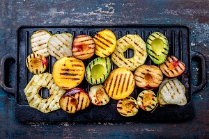 GRILLED FRUITS. Grill fruits - pineapple, peaches, plums, avocado, pear on black cast iron grill board