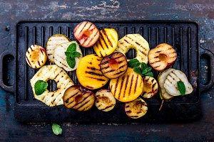 GRILLED FRUITS. Grill fruits - pineapple, peaches, plums, avocado, pear with mint on black cast iron grill board