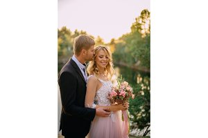 happy newlyweds standing against nature background at sunset