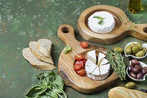 Camembert and olives on wooden boards
