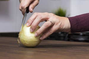 Woman chopping an onion.