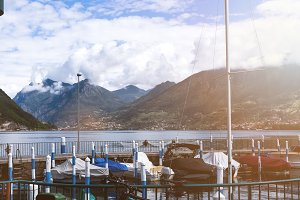 Boats in the harbor on Lake Iseo with a view of the mountains and the sky with voluminous clouds - travel and natural background.