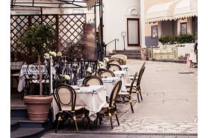 View of a cozy cafe with rattan furniture on a European old street - travel and vacation background