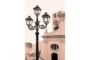 Old street lamp on a background of the European church with a dial and a bell. Cheron-white toned photo - architectural background