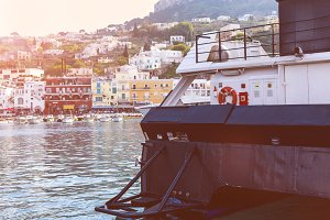Part of the ship close-up on the background of the bay and the coast with colorful houses - travel background