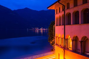 Night Italian city: a building with arches illuminated and a view of the lake.